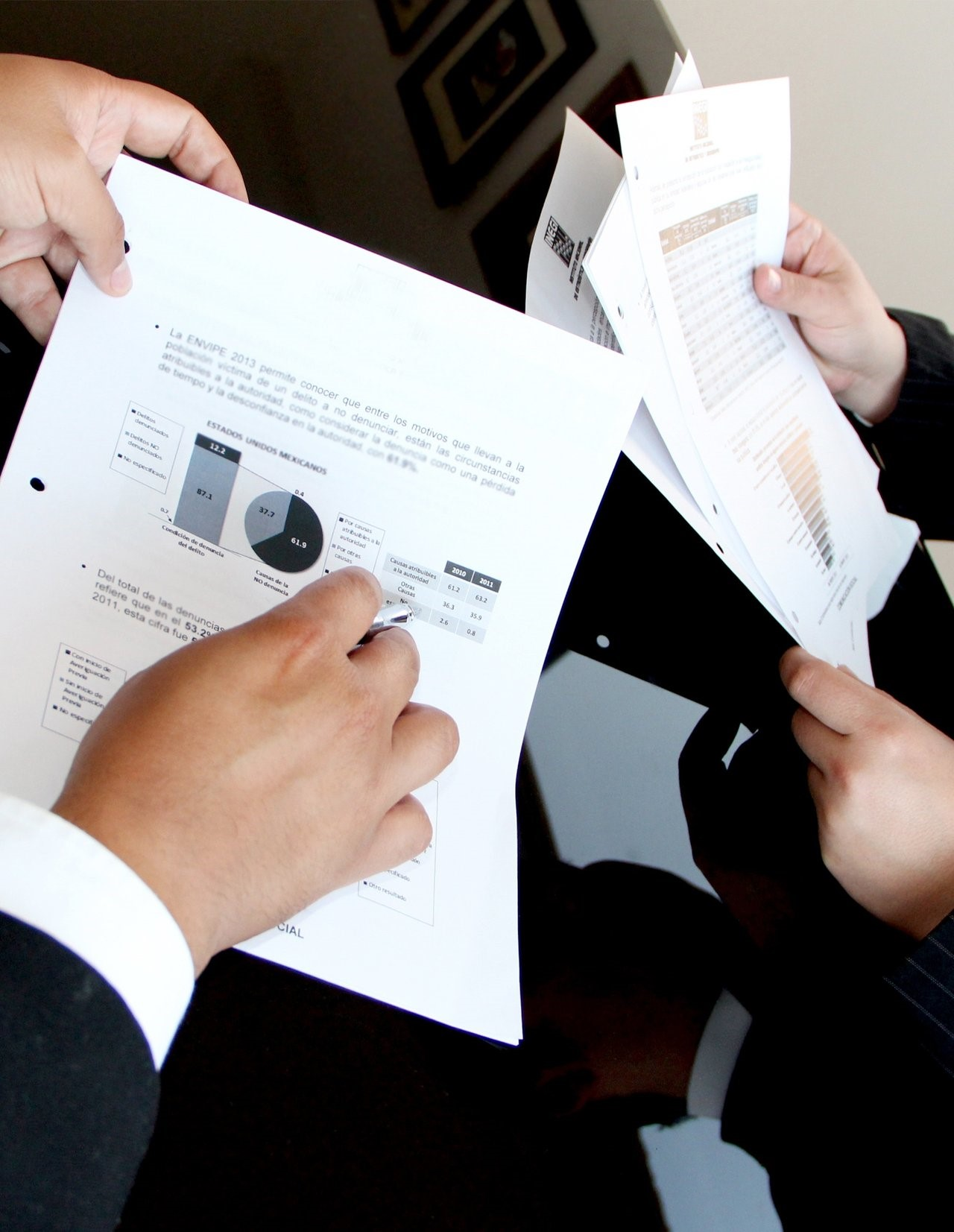 People holding documents with statistics