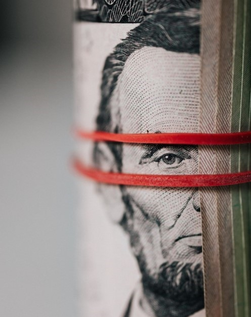 Roll of five dollar bills with rubber band around it
