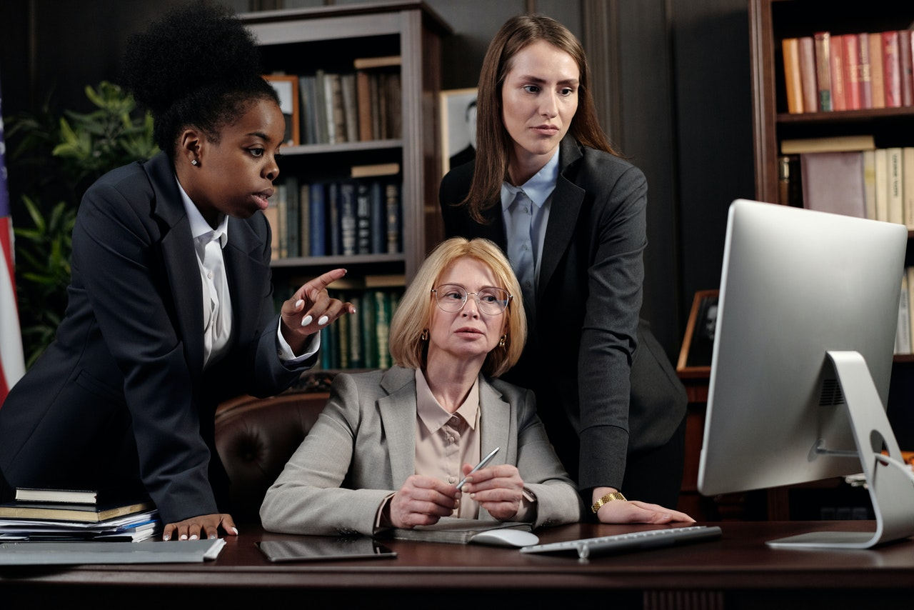 Three people around a computer at a legal office