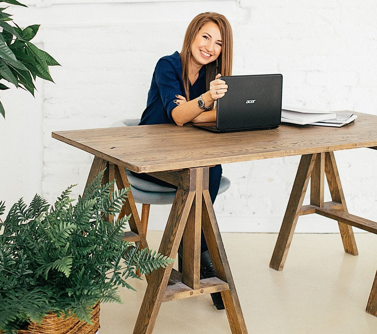 Woman sitting at table in front of laptop