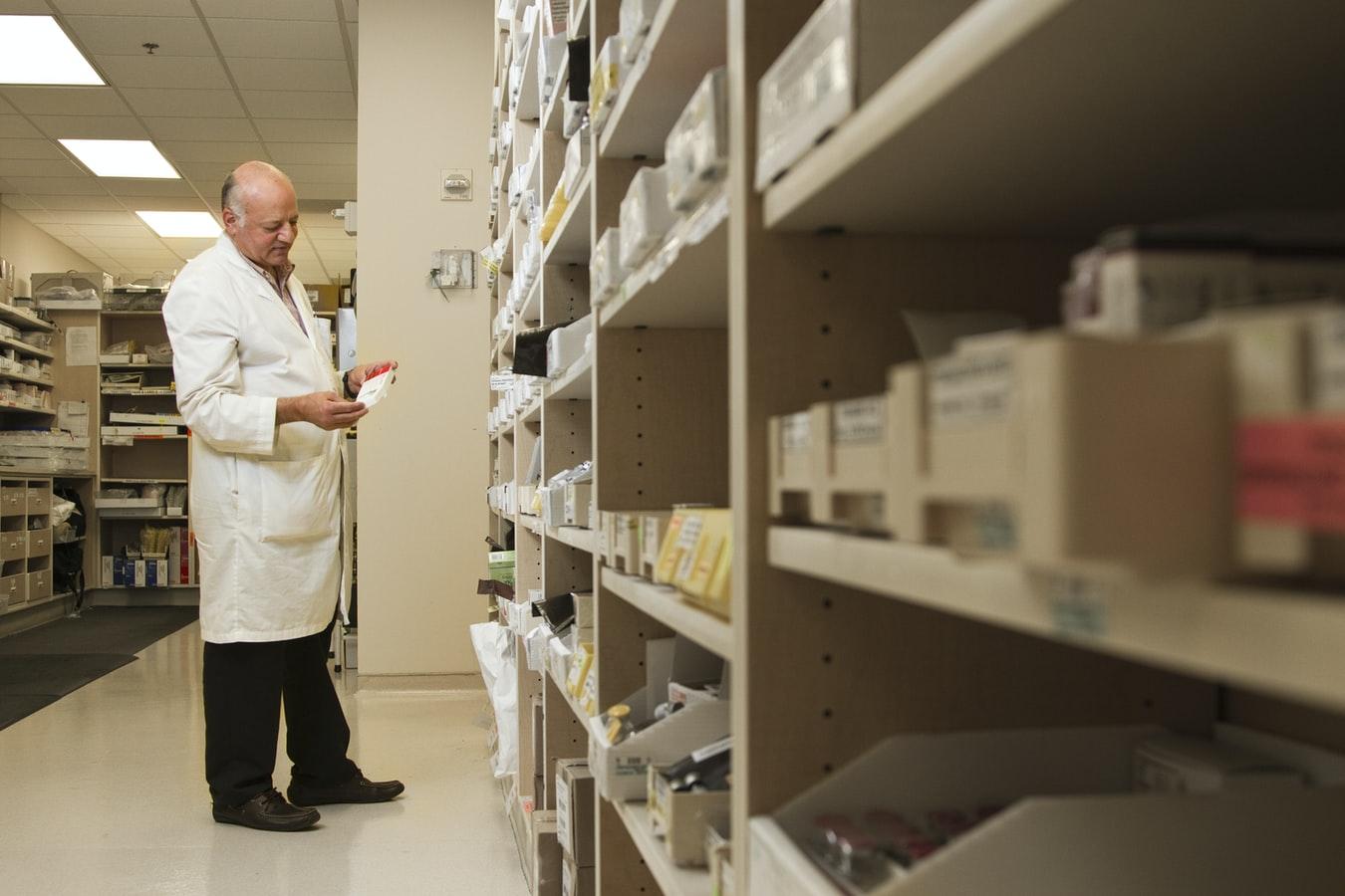 Pharmacist standing in front of shelves