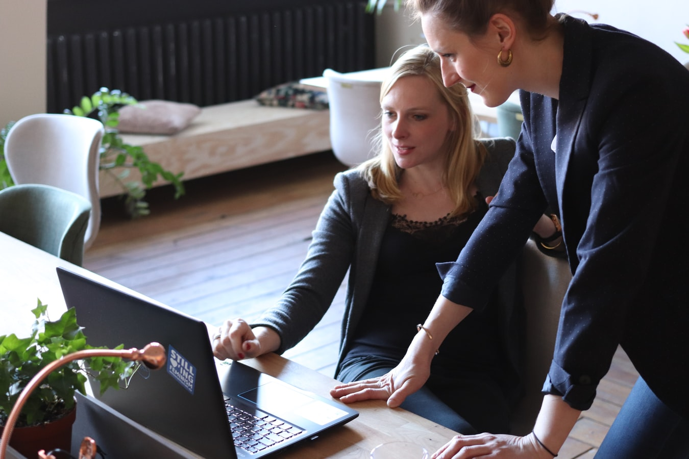 Two people sitting in front of a laptop