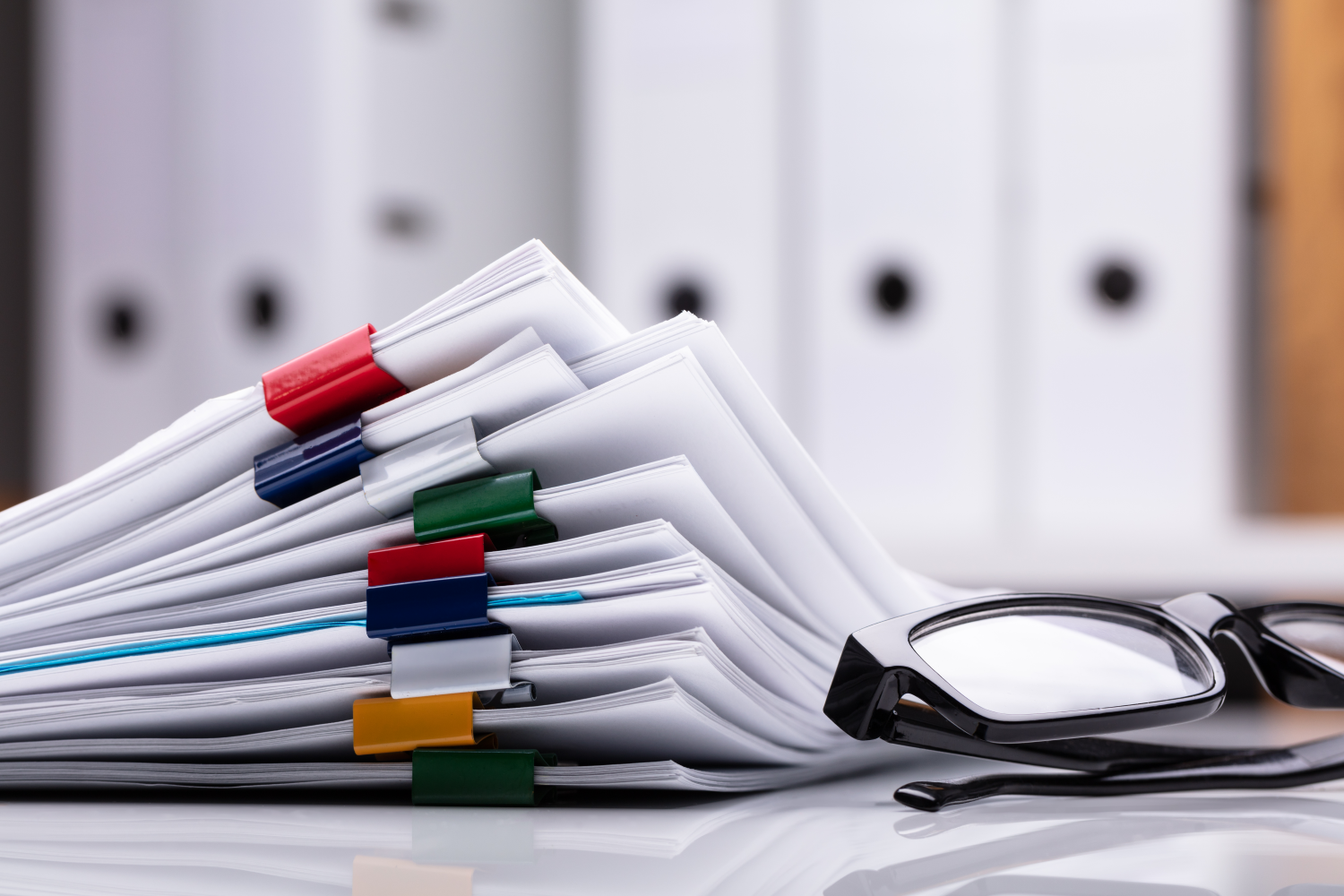 Stack of documents with eyeglasses beside them