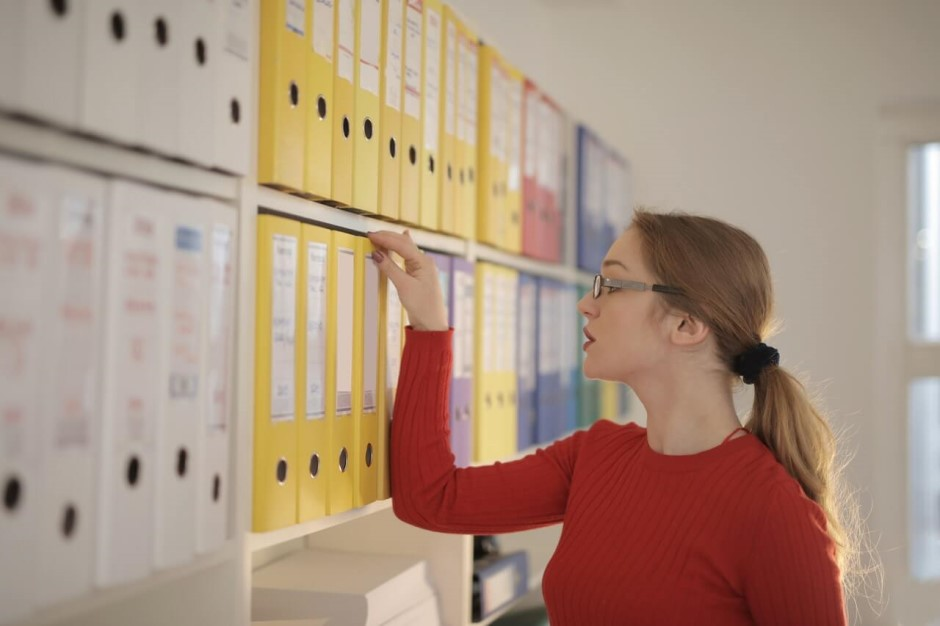 Woman looking at files on a shelf