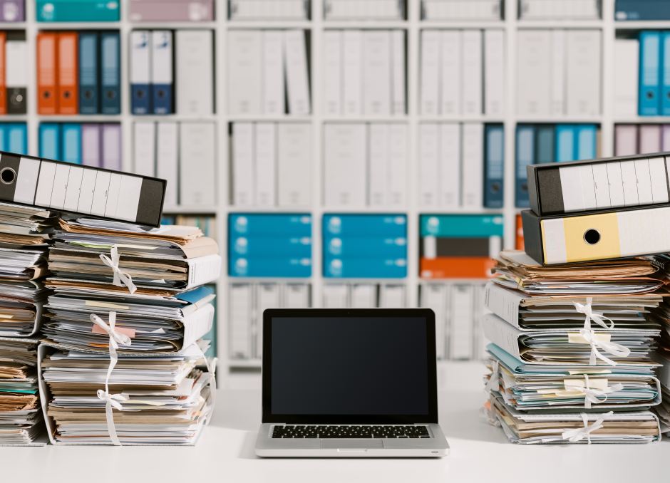 Stacks of documents with a laptop in the middle