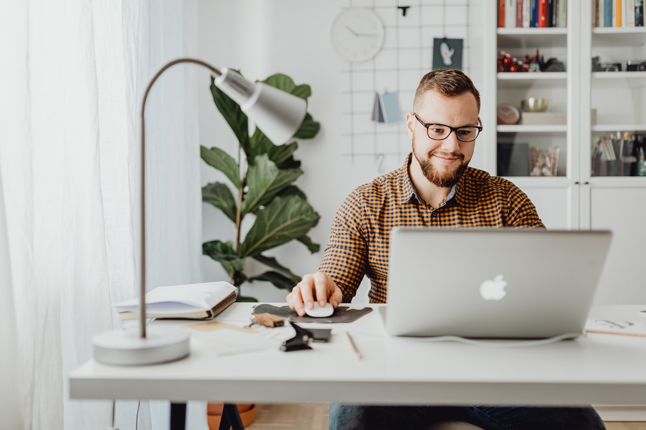 An employee smiling and checking on his home laptop Document Automation for Workday software