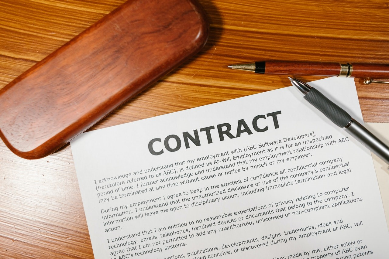 Example contract created placed on a desk with a pen beside it