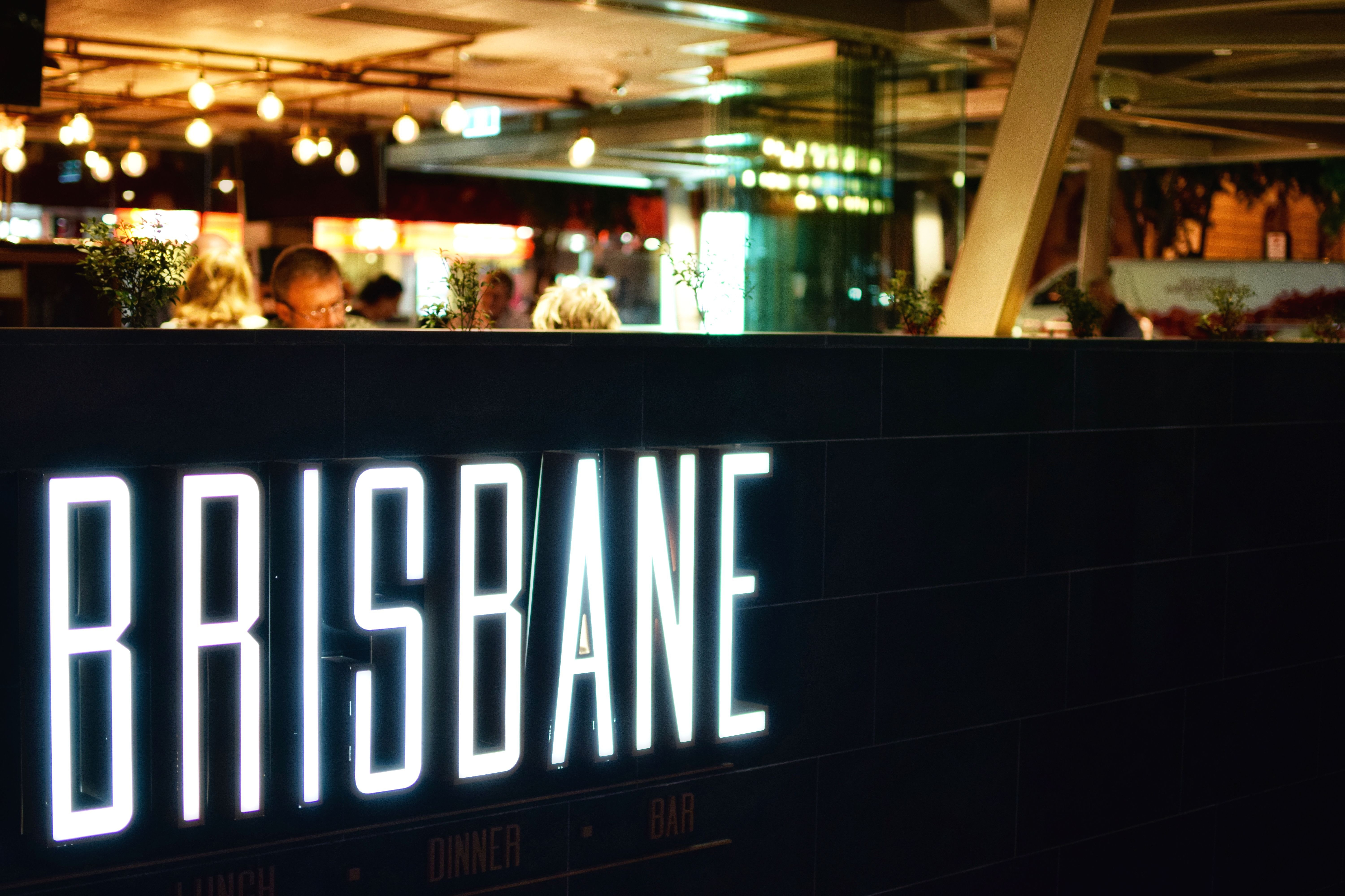 Diners sit inside a sports club with illuminated Brisbane sign oblivious to professional pest control services