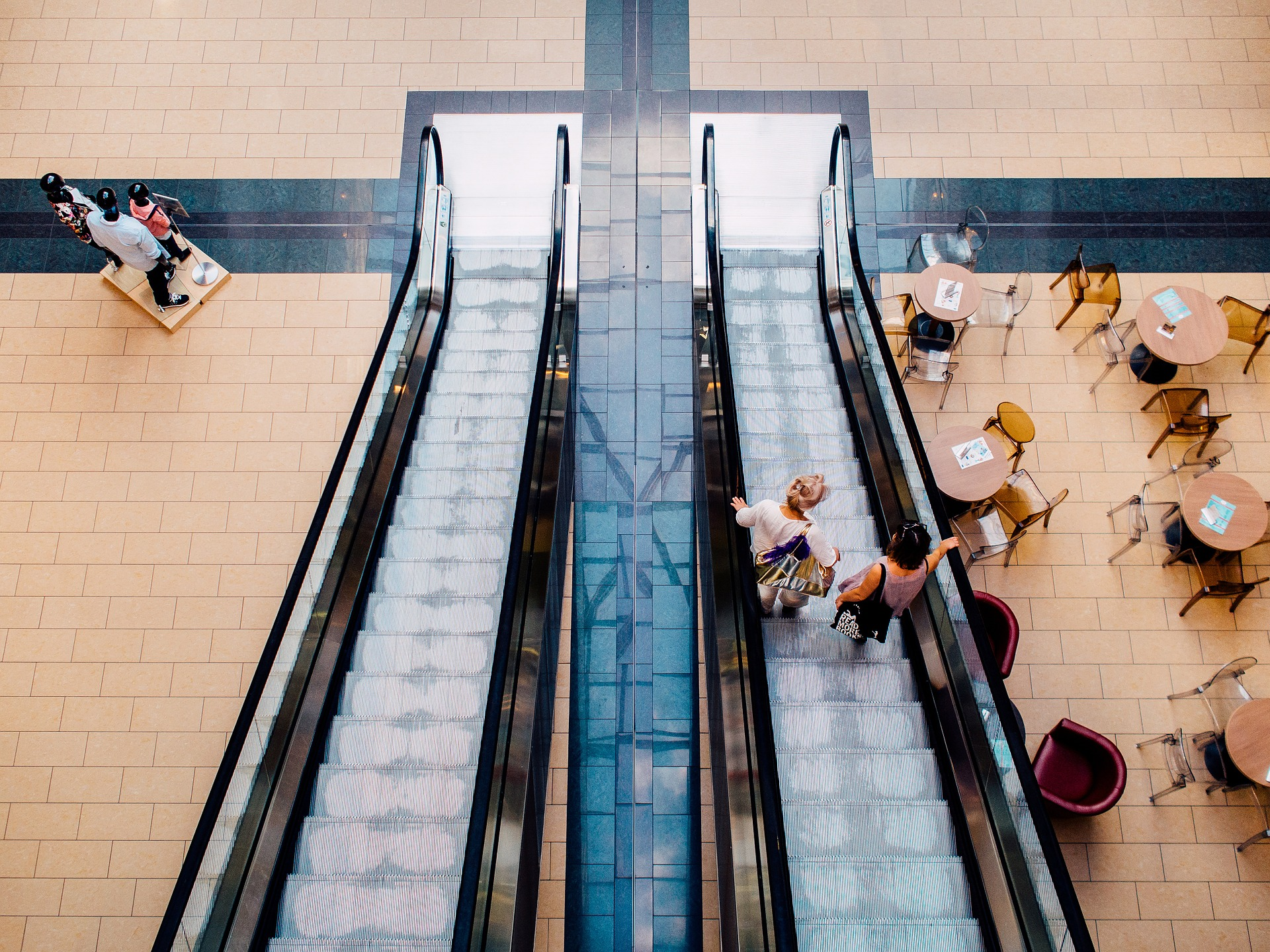 Two women stand on an elevator with cafe tables to one side and store mannequins on the other where Integrated Pest Management works best for shopping centre pest control