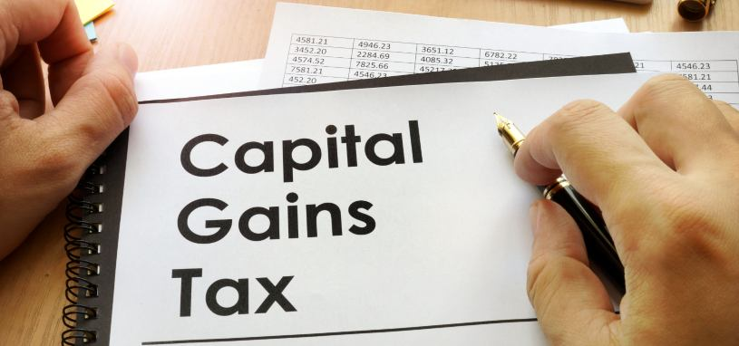 capital gains tax written on a piece of paper on top of financial documents
