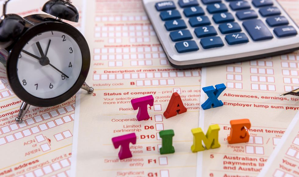 calculator and clock on top of annual australian company tax forms
