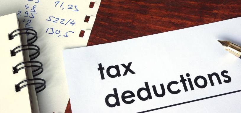 the phrase tax deductions written on paper beside financial figures