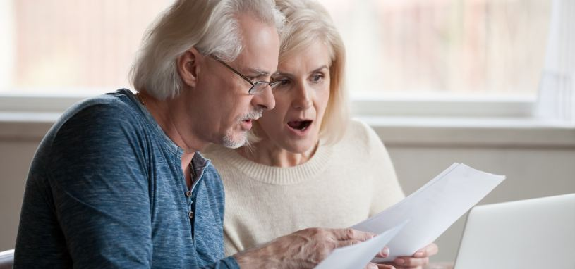 couple looking surprised whilst looking at company documents
