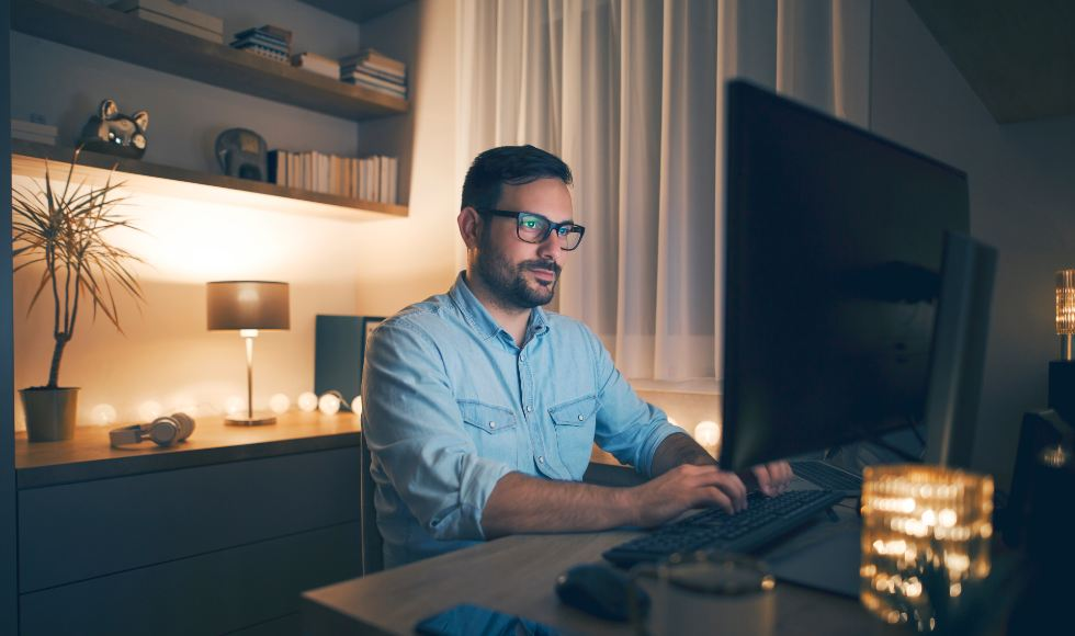 man working from home sitting at computer desk
