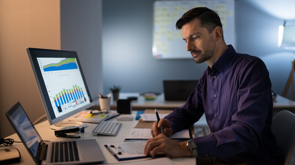 man at desk looking over KPIs