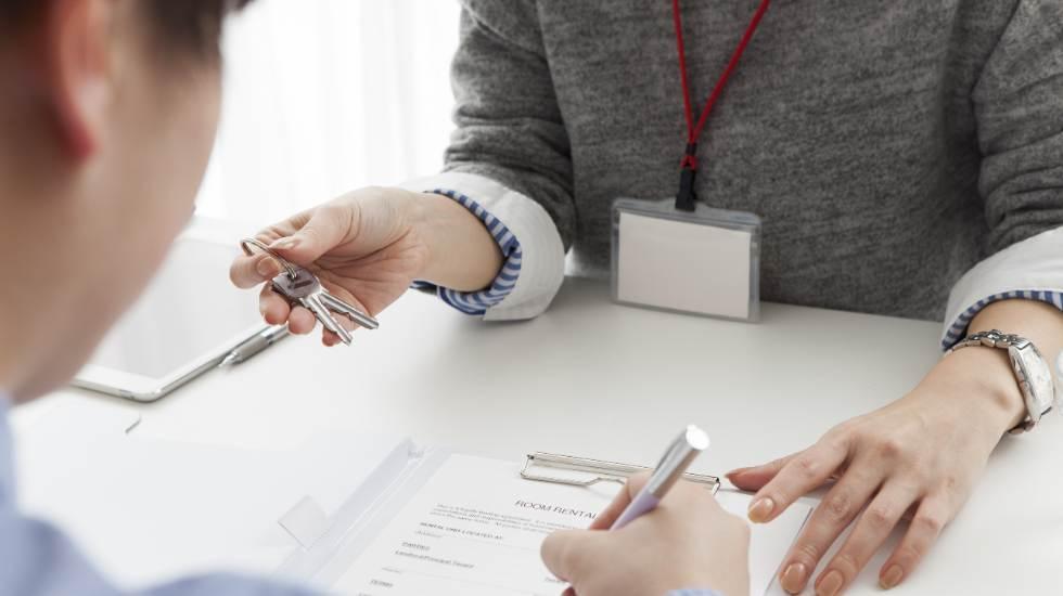 Woman holding keys man signing document