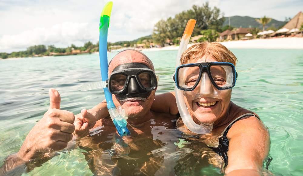 happy retired couple taking selfie in tropical sea