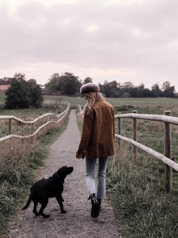 Kvinna med hatt i naturen med sin hund