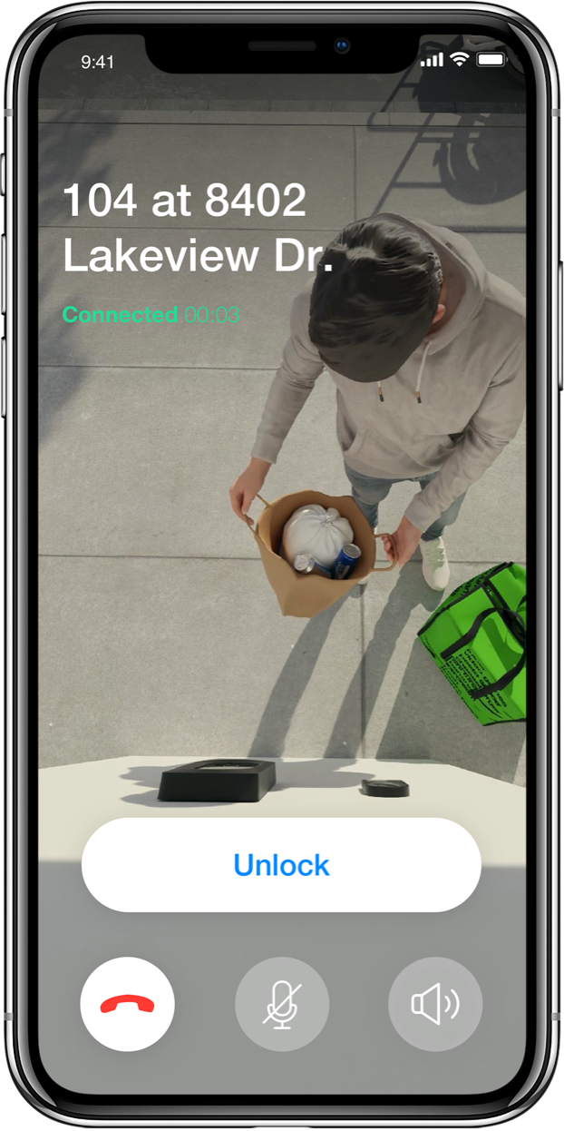 A delivery man standing outside a building is shown on a phone screen with controls to unlock or communicate with the delivery person.