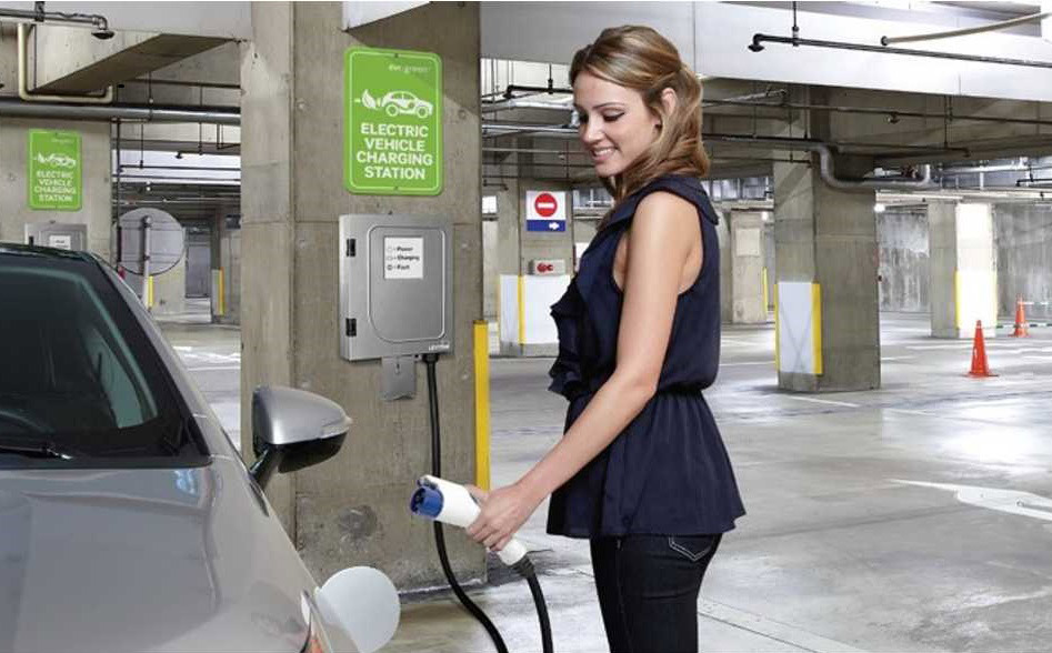 Women charging her electric vehicle from a EV charging station installed at her office parking garage
