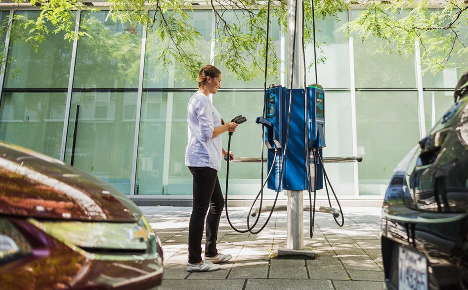Women charging her electric vehicle from a EV charging station installed at a public charging station