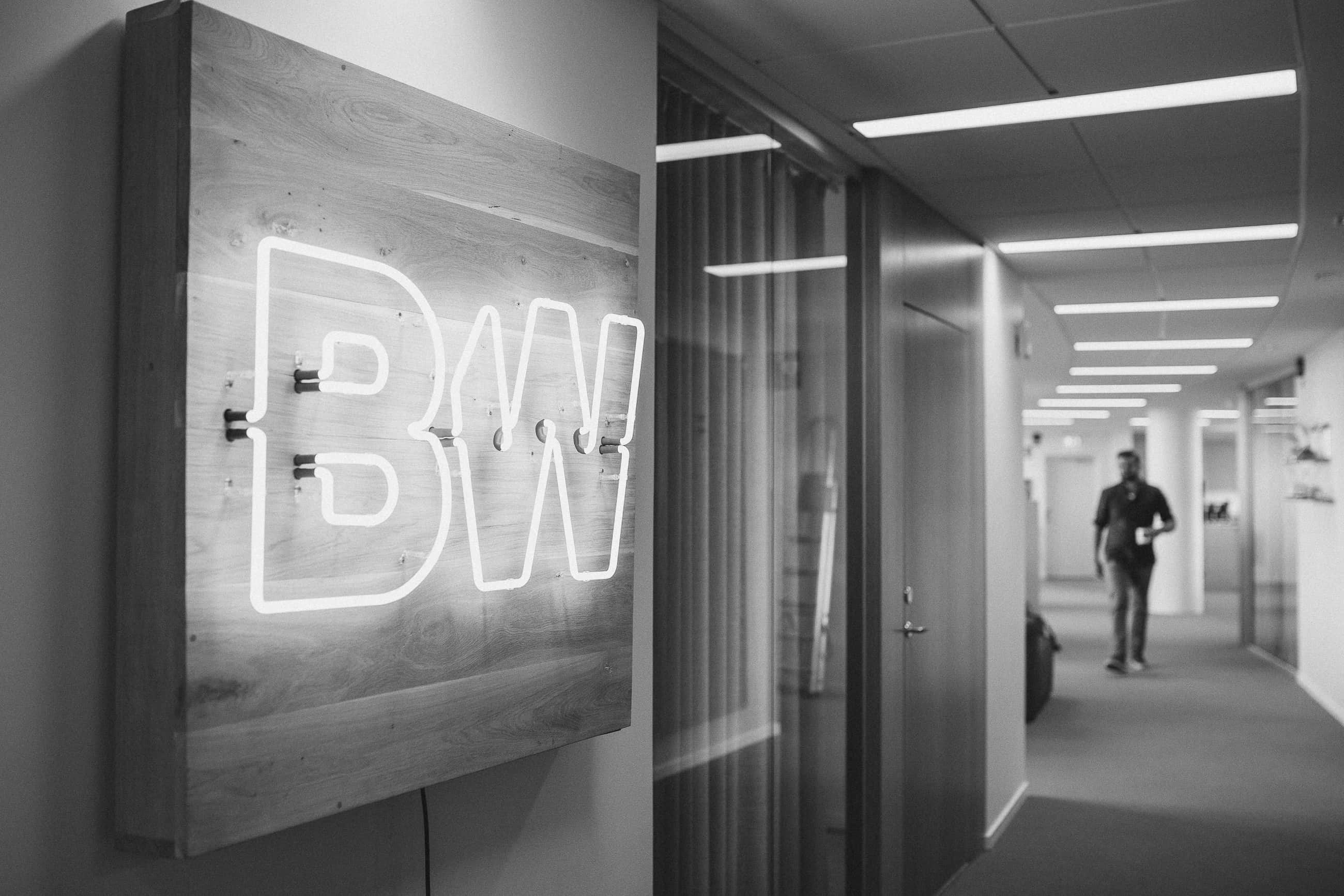 Black and white image featuring the Bombayworks logo on a neon sign in the Malmö office.