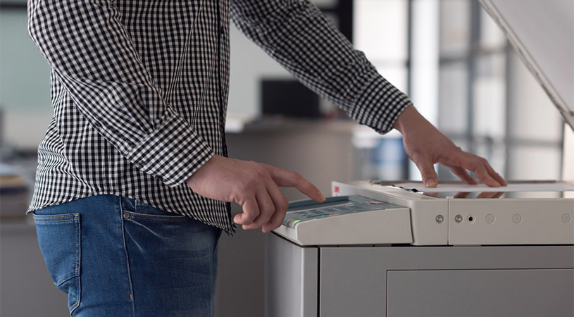 man pressing button on photocopier
