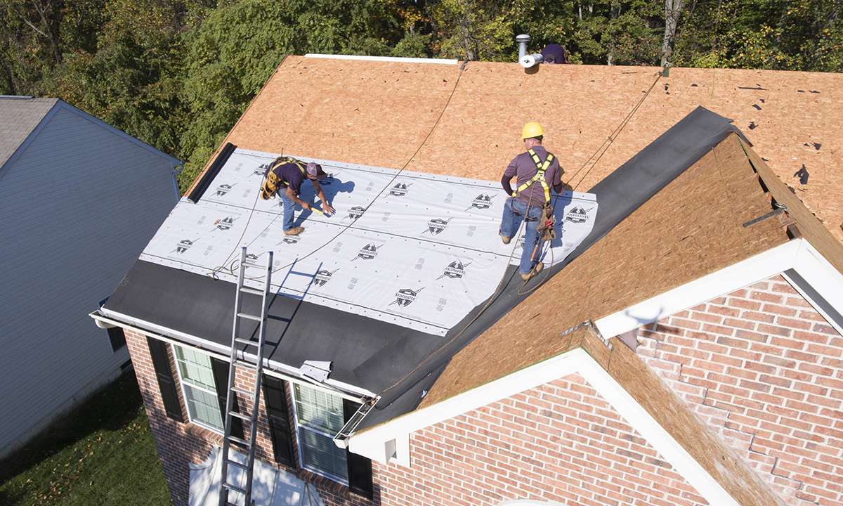 two roofers intalling roof underlayment