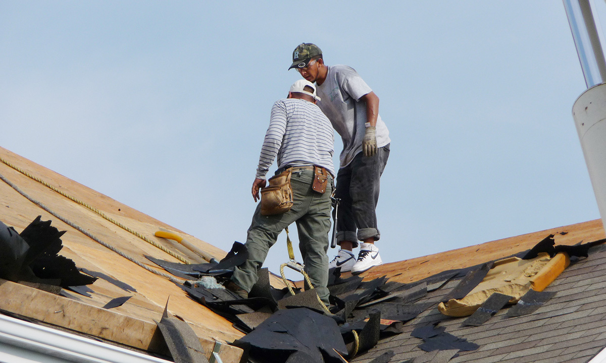 two roofers doing a tear off on a roof