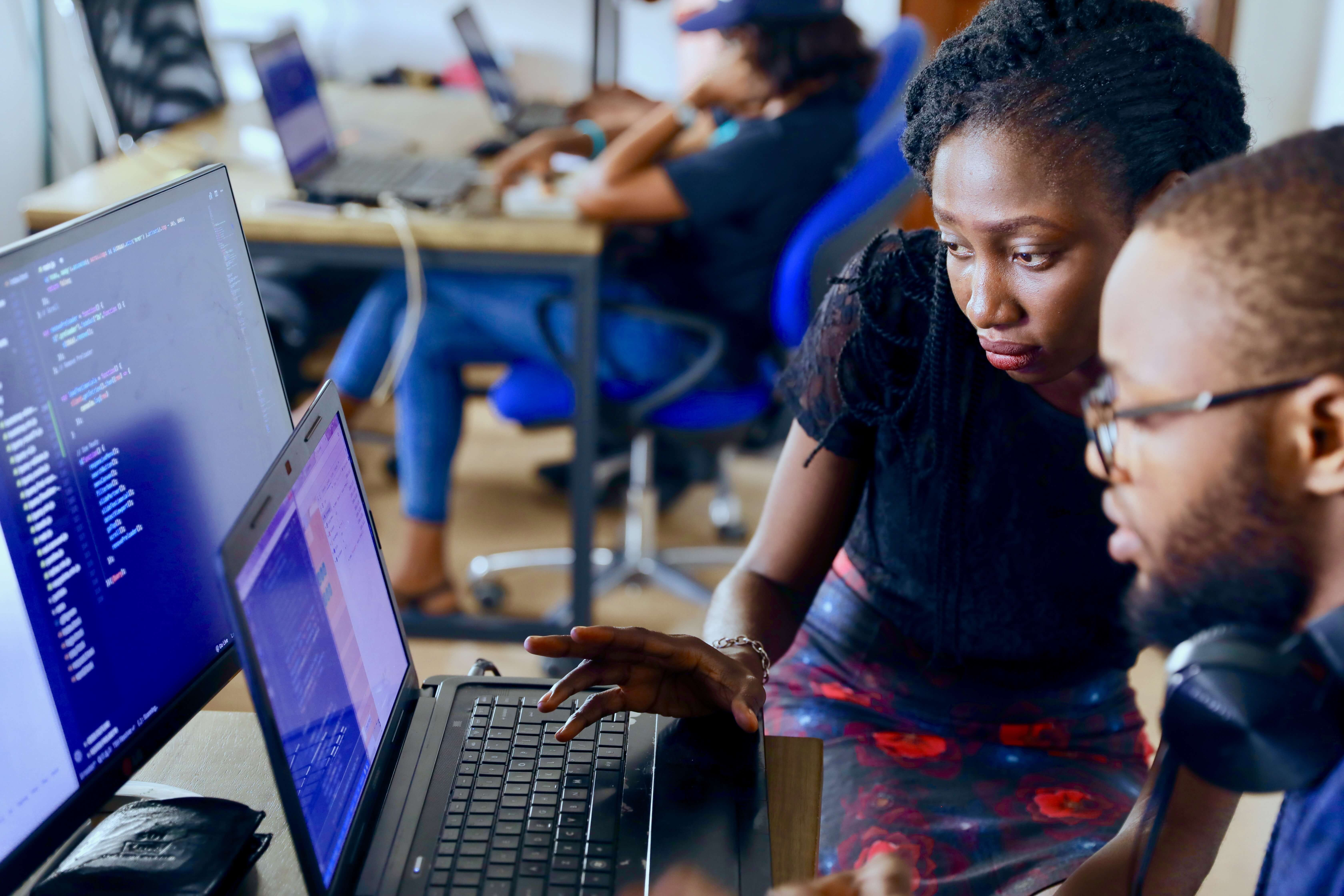 Young woman showing something to a colleague in front of a laptop