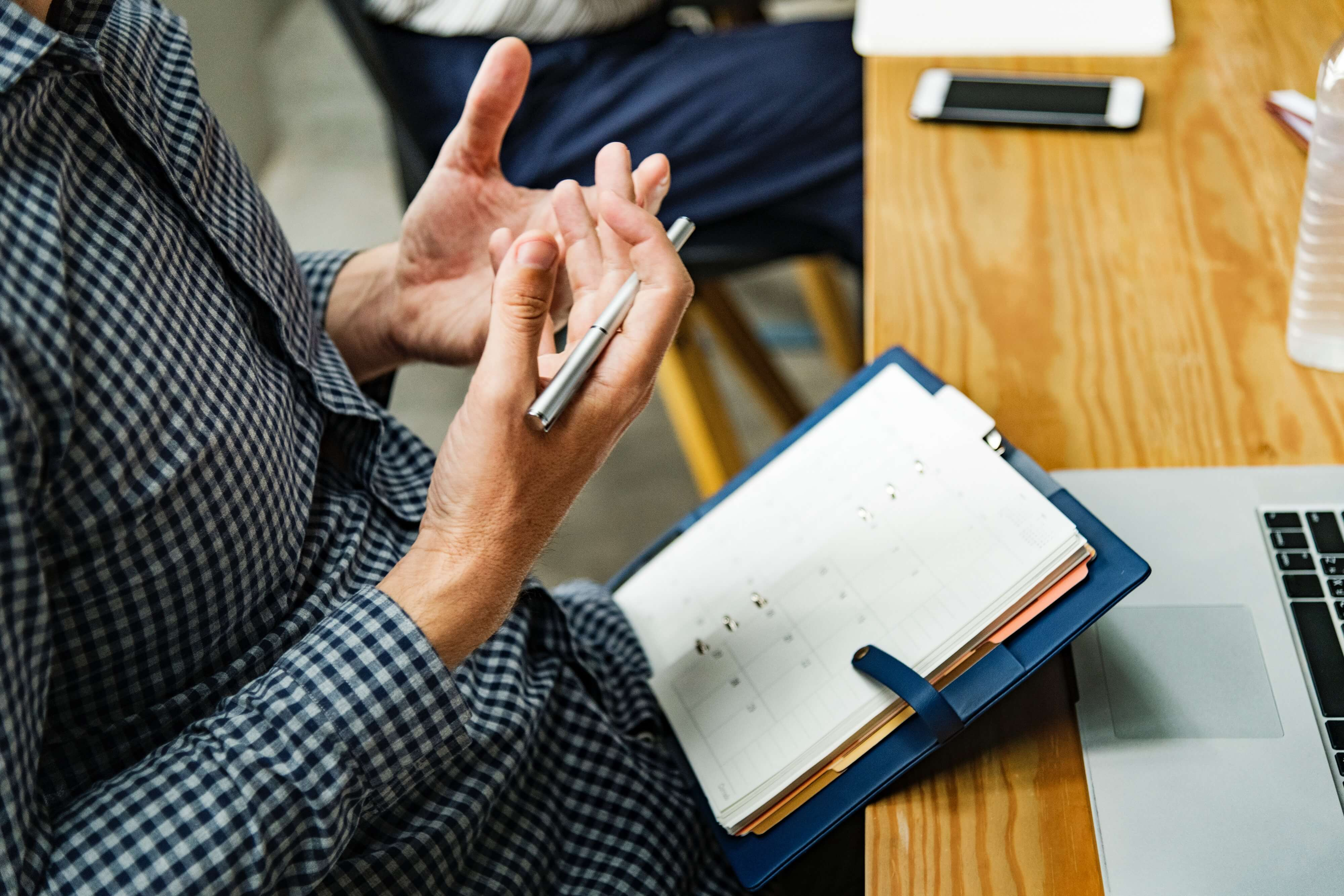 Hands of a person explaining something in front of his agenda
