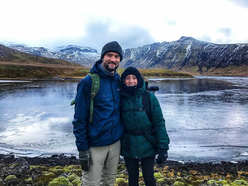 Man & woman standing in front of water in Iceland.