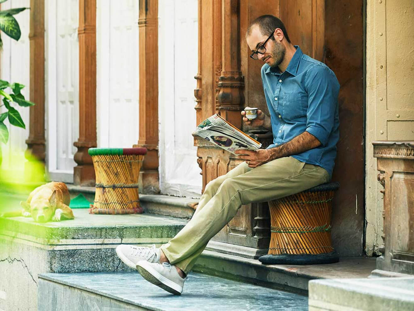 Scott Keyes drinking tea & reading newspaper.