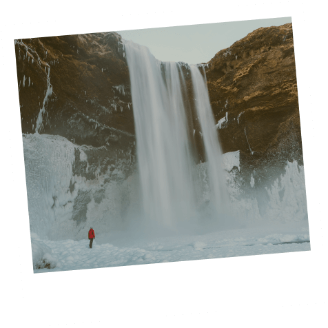 Person overlooking frozen waterfall.