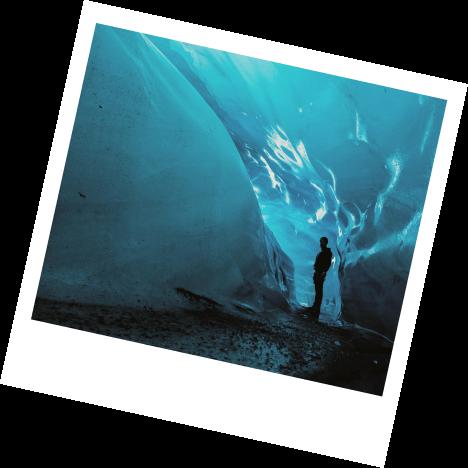 Person walking next to glacier.