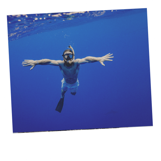 Person in blue water snorkeling.