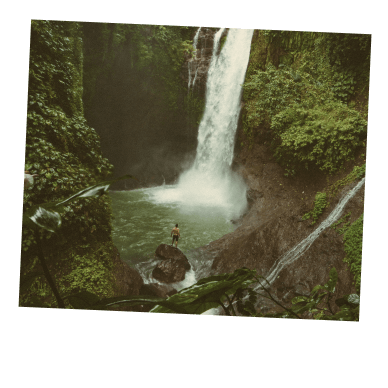 Person standing on rock overlooking waterfall.
