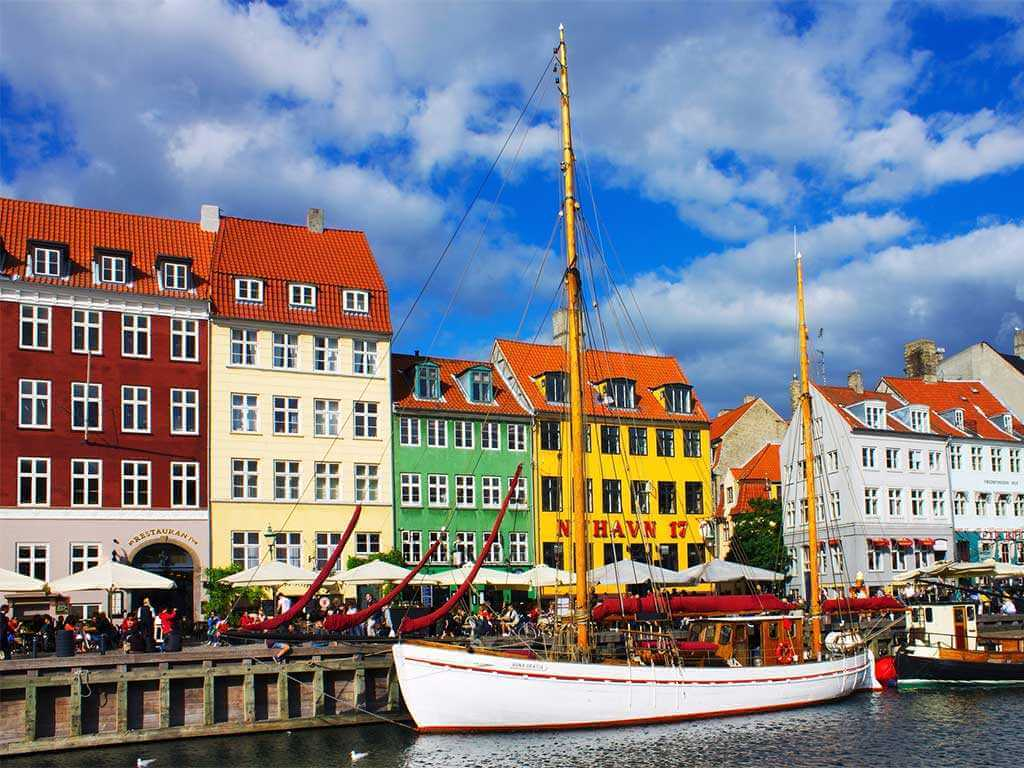 White sailboat in the harbor in Copenhagen with colorful buildings in the background
