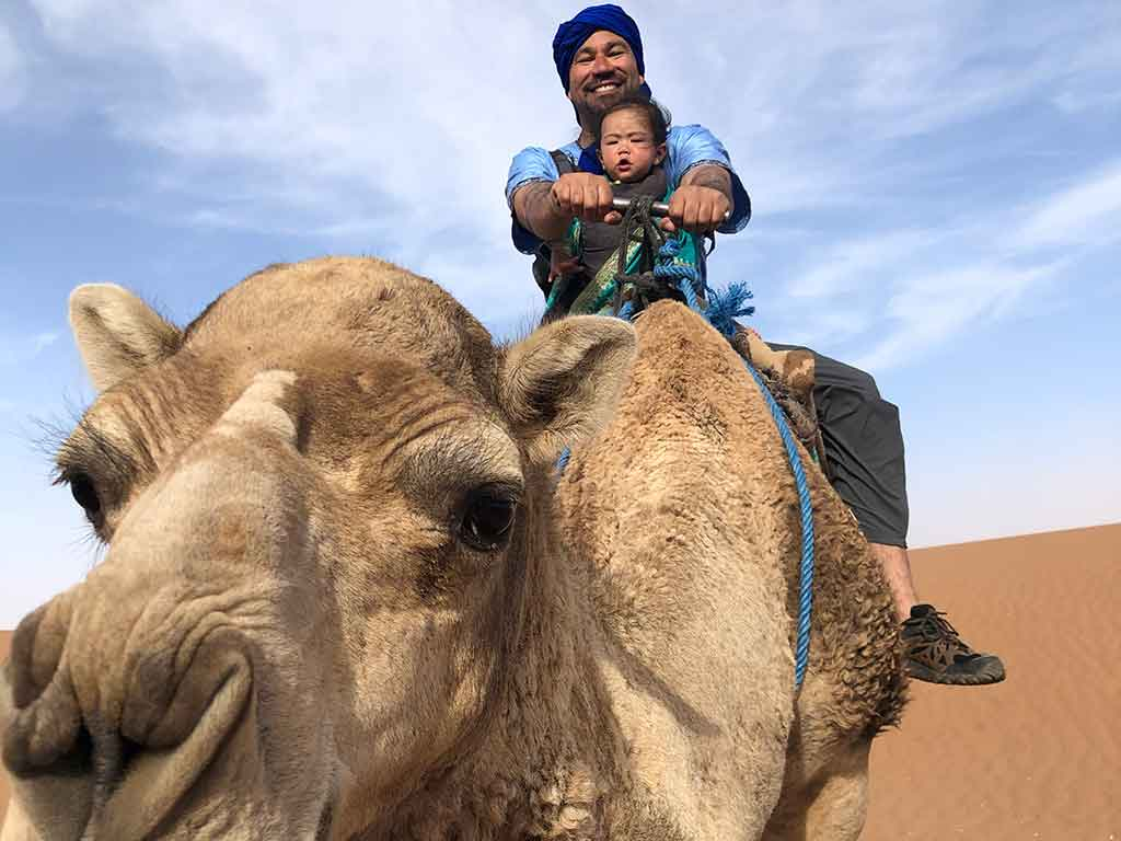 Man and toddler riding a camel in Morocco.
