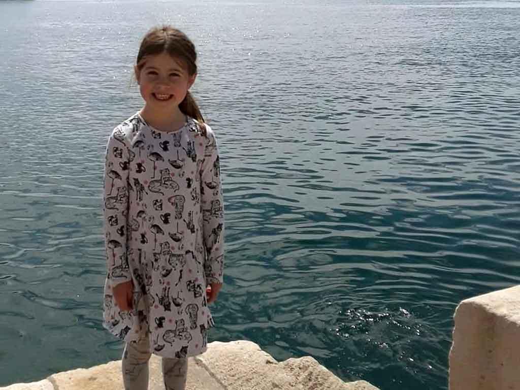 Girl standing on dock in Croatia.