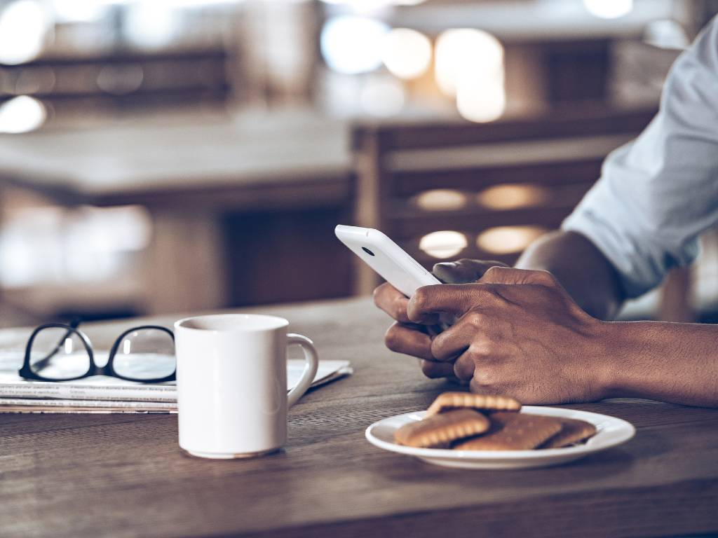 man's hands holding cellphone on table with his glasses and coffee
