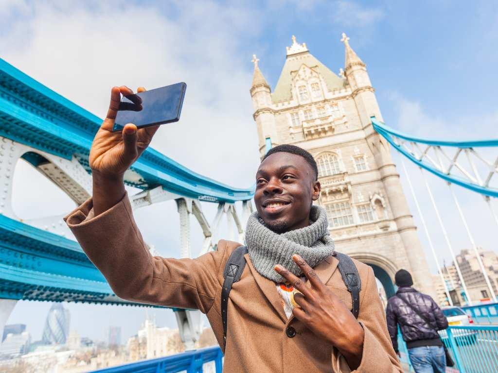 smiling man taking selfie in front of London Bridge.