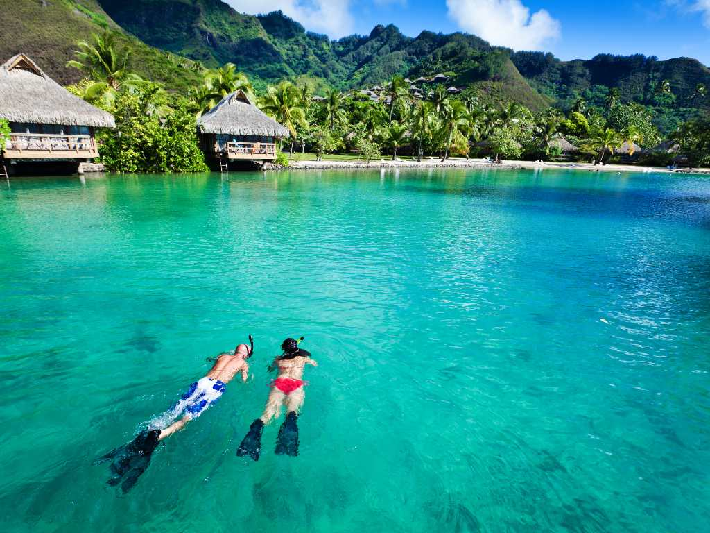 Young couple snorkeling in clean water over coral reef.