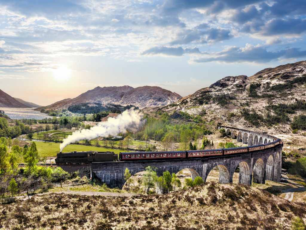 Glenfinnan Railway Viaduct in Scotland with the Jacobite steam train against sunset over lake.