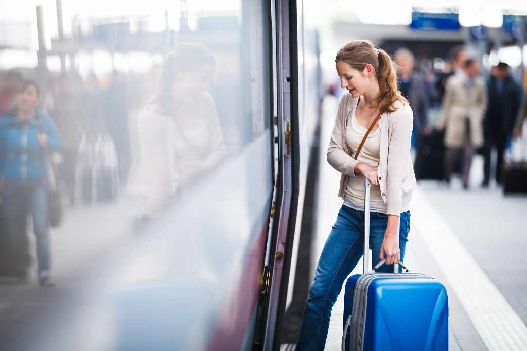 young woman boarding train with luggage.