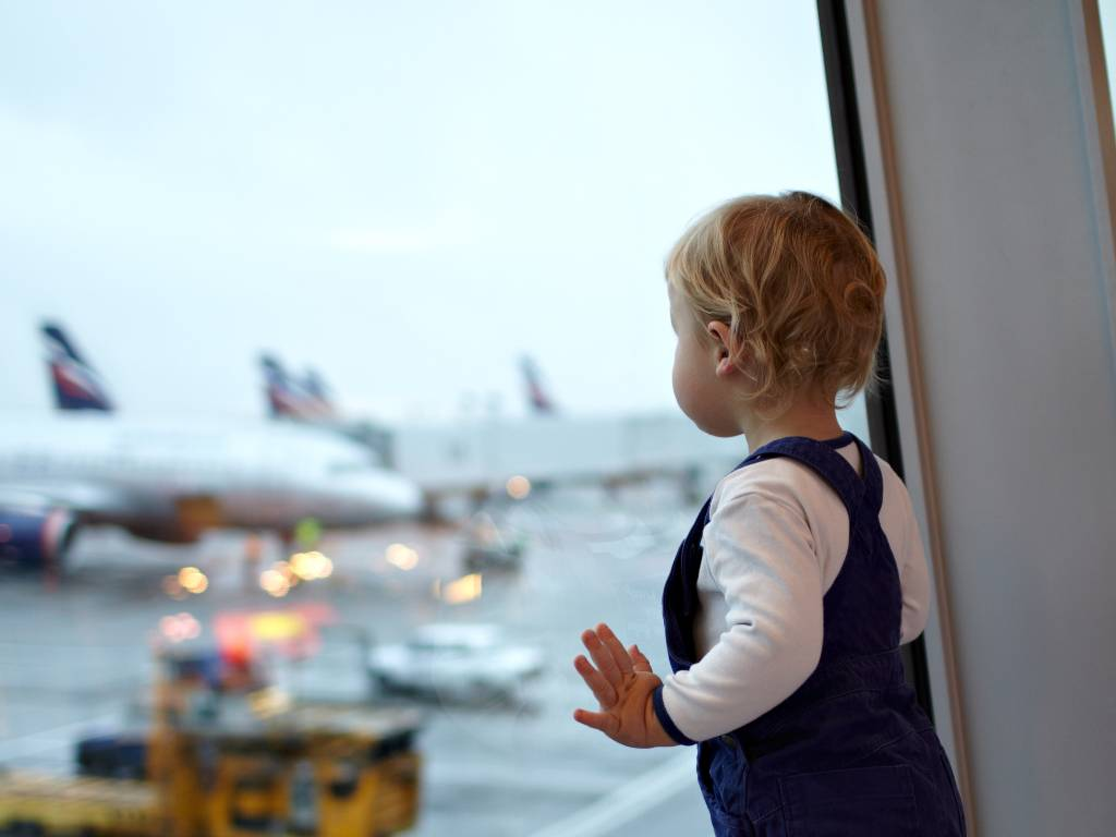 baby watching planes out the window at airport