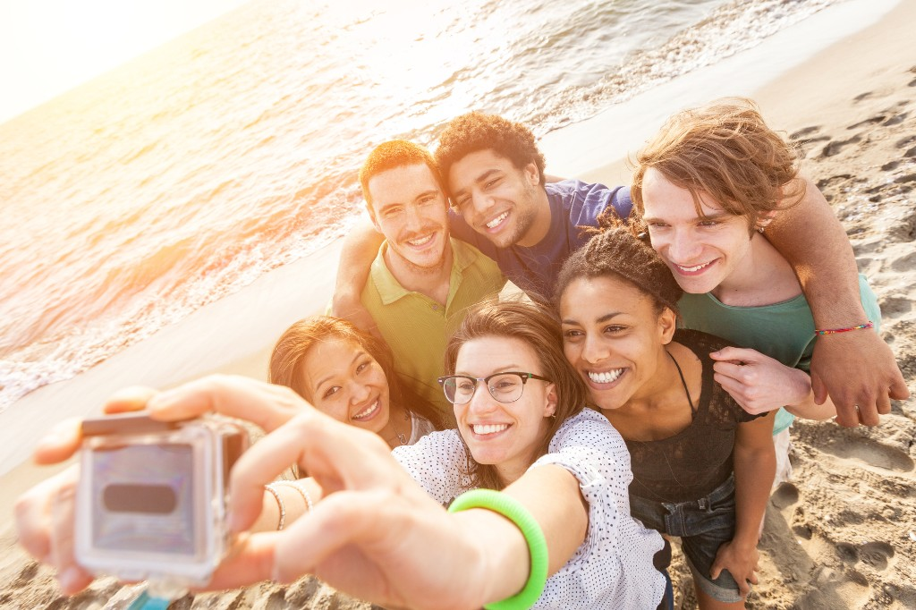 group of travelers taking selfie on the beach.