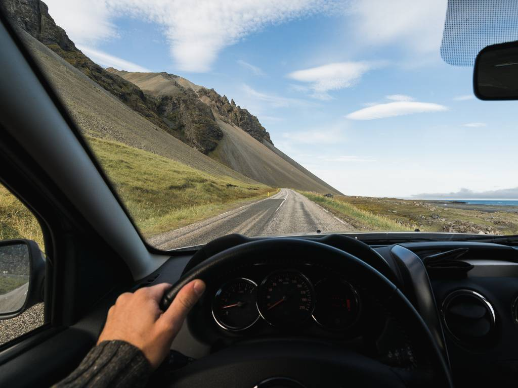 view through driver's window of road in Iceland.