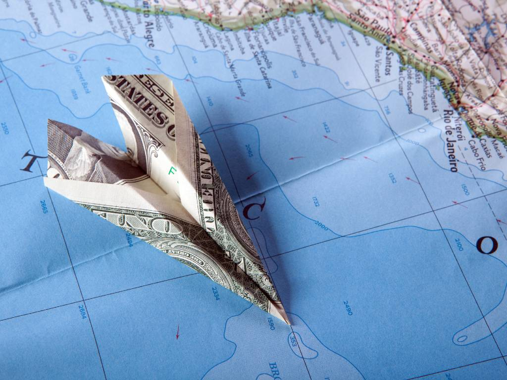 paper plane made of dollar bill sitting on map.