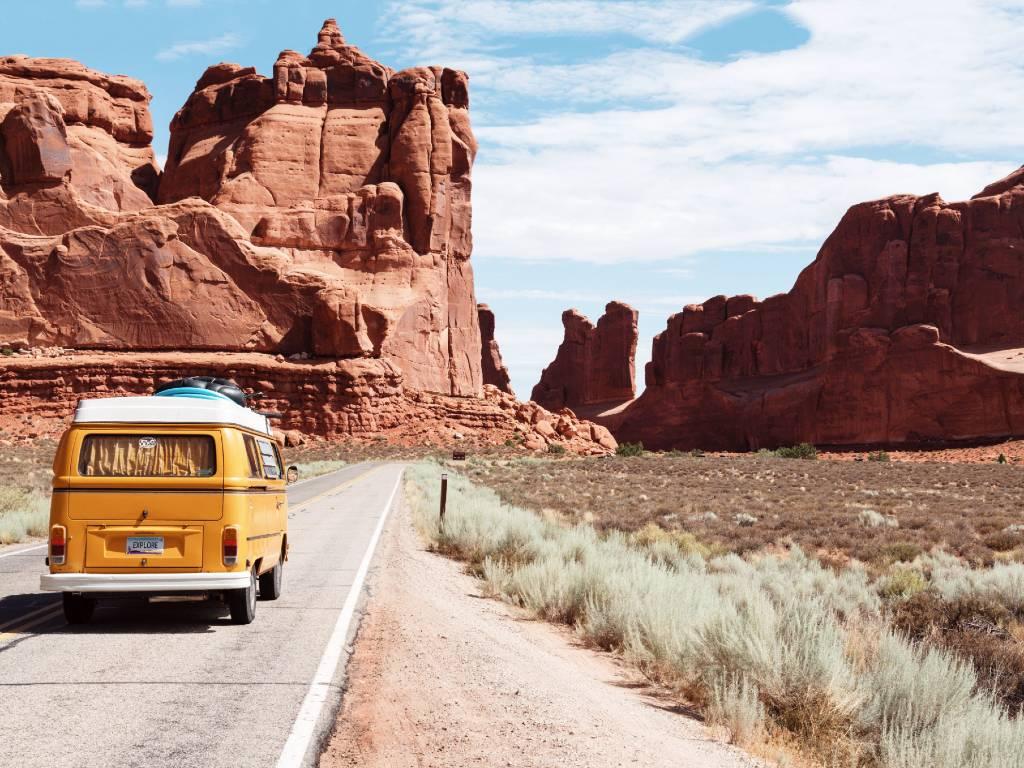 yellow van driving on road in the desert.